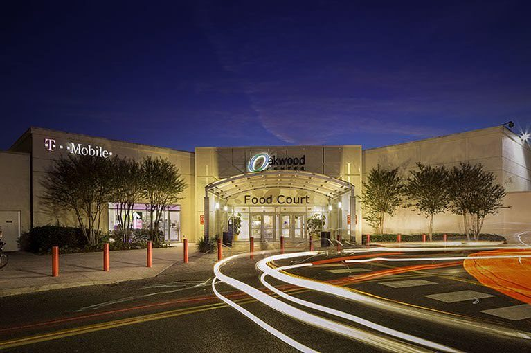 The food court entrance to Oakwood Center is lit up at night.